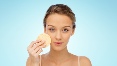 removing make up: beauty, people and skincare concept - young woman cleaning face with exfoliating sponge over blue background