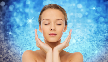 young woman face: beauty, people, skincare and health concept - young woman face and hands over blue holidays lights or glitter background Stock Photo