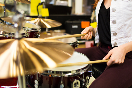 cymbals: music, sale, people, musical instruments and entertainment concept - close up of female musician playing cymbals at music store Stock Photo