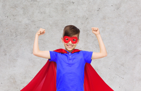 pre teen boy: carnival, childhood, power, gesture and people concept - happy boy in red super hero cape and mask showing fists over gray background Stock Photo