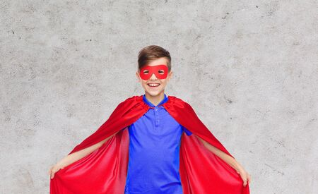 pre adolescent boys: carnival, childhood, power and people concept - happy boy in red super hero cape and mask over gray background