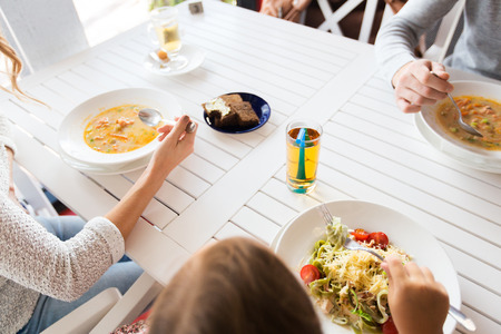 parenthood, communication and people concept - close up of family with child having dinner at restaurant or cafe