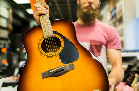 entertainment concept: music, sale, people, musical instruments and entertainment concept - close up of male assistant or customer with beard holding acoustic guitar at music store