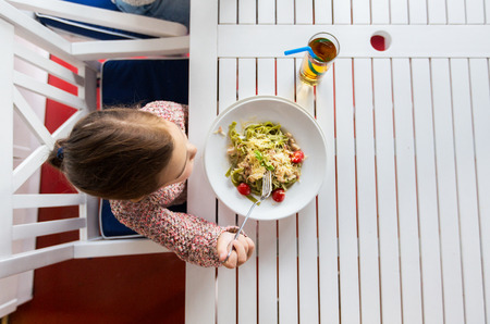children eating: childhood, food and people concept - little girl eating pasta for dinner at restaurant or cafe