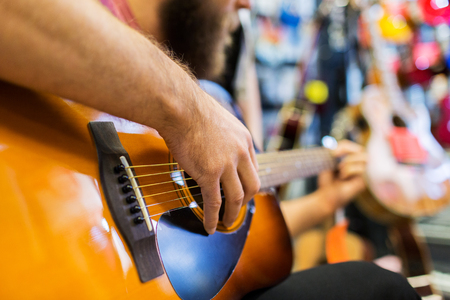 entertainment concept: music, sale, people, musical instruments and entertainment concept - close up of man playing guitar at music store Stock Photo