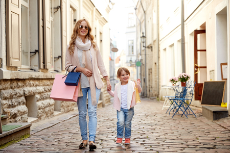 old city: sale, consumerism and people concept - happy mother and child with shopping bags walking along city street