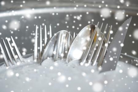 lavar trastes: tareas del hogar, lavar los platos y la limpieza concepto - cerca de platos sucios en el fregadero de la cocina de lavado sobre el efecto de la nieve