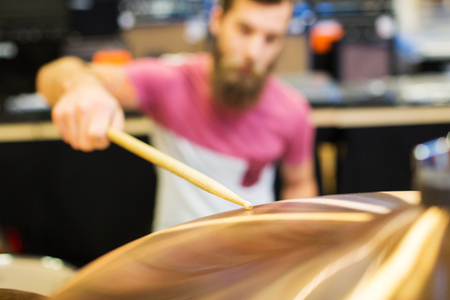 cymbals: music, sale, people, musical instruments and entertainment concept - close up of male musician playing cymbals at music store
