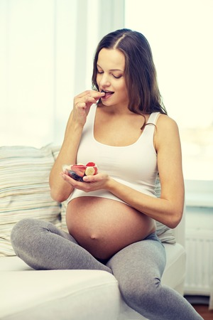 woman eating fruit: pregnancy, food, healthy eating, people and expectation concept - happy pregnant woman eating fruits at home