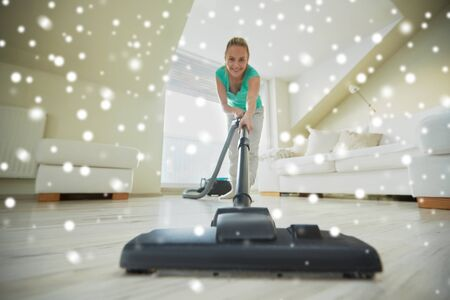 household chores: people, housework and housekeeping concept - happy woman with vacuum cleaner at home over snow effect Stock Photo