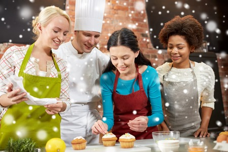 cooking class, culinary, bakery, food and people concept - happy group of women and male chef cook baking in kitchen over snow effect