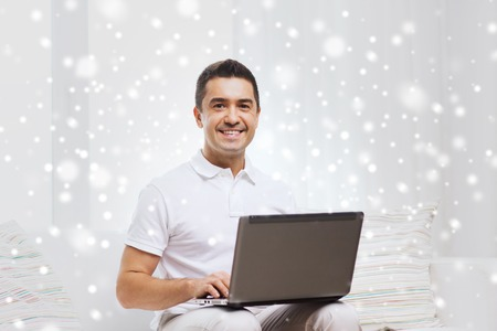 mid distance: technology, people lifestyle and networking concept - happy man working with laptop computer at home over snow effect