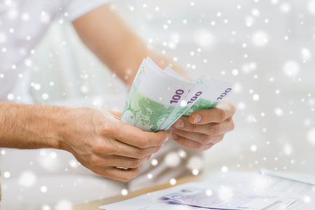 home finances: savings, finances, economy and home concept - close up of man hands counting money at home over snow effect