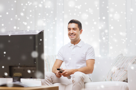 entertainment concept: home, people, technology and entertainment concept - smiling man with remote control watching tv at home over snow effect