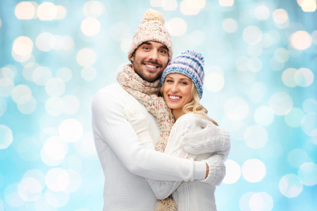 latin family: winter, love, couple, christmas and people concept - smiling man and woman in hats and scarf hugging over blue holidays lights background