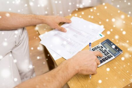 business savings: business, savings, finances and people concept - close up of man hands with papers and calculator at home over snow effect