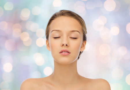 beauty, people and health concept - young woman face with closed eyes and shoulders over blue holidays lights background
