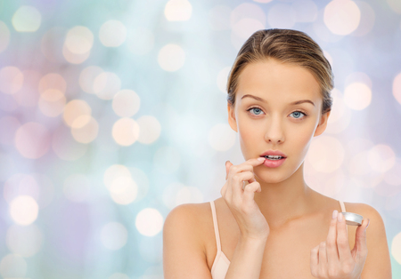 gloss: beauty, people and lip care concept - young woman applying lip balm to her lips over blue holidays lights background