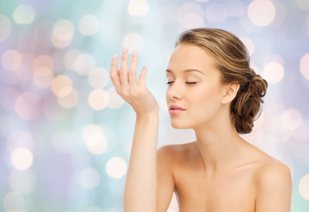 fragrant: beauty, aroma, people and body care concept - young woman smelling perfume from wrist of her hand over blue holidays lights background Stock Photo
