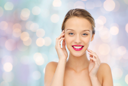 beauty face: beauty, people and health concept - smiling young woman face with pink lipstick on lips and shoulders over blue holidays lights background Stock Photo