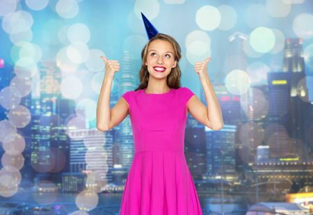 party night: people, holidays and celebration concept - happy young woman or teen girl in pink dress and party cap over night city and holidays lights background