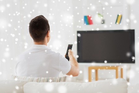 leisure, technology, mass media and people concept - man watching tv and changing channels at home from back over snow effect Stock Photo