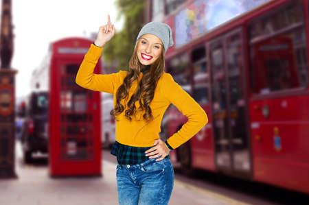 moda ropa: las personas, los viajes, el turismo y el concepto de moda - mujer joven feliz o chica adolescente en ropa casual y sombrero de última moda que destaca el dedo sobre el fondo londres calle de la ciudad