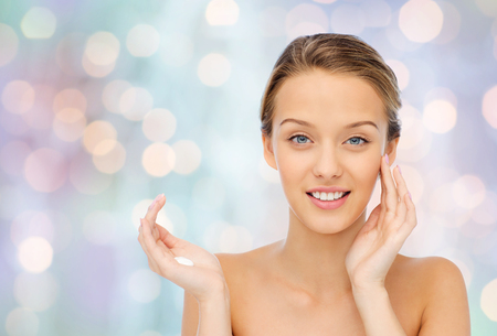 beautiful background: beauty, people, cosmetics, skincare and health concept - happy smiling young woman applying cream to her face over blue holidays lights background Stock Photo