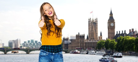 posing  agree: people, gesture, travel, tourism and fashion concept - happy young woman or teen girl in casual clothes showing thumbs up over thames river bridge and big ben in london city background