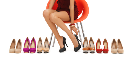 high up: people, fashion, shopping, footwear and style - close up of woman sitting on chair and trying on high heeled shoes