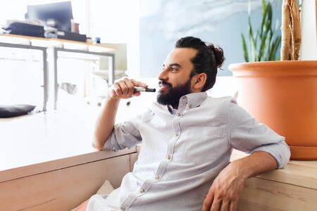 business, startup, inspiration and people concept - happy latin man with beard and hair bun at office