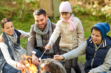 camping, travel, tourism, hike and people concept - happy family roasting marshmallow over campfire Archivio Fotografico