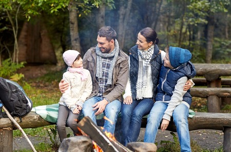 sitting people: camping, travel, tourism, hike and people concept - happy family sitting on bench and talking at camp near campfire in woods