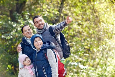 aventura, viajes, turismo, ir de excursión y la gente concepto - familia feliz caminando con mochilas en maderas Foto de archivo
