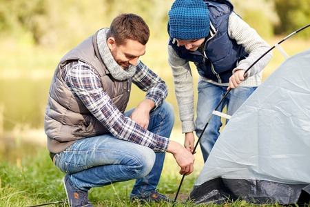 setting: camping, tourism, hike, family and people concept - happy father and son setting up tent outdoors