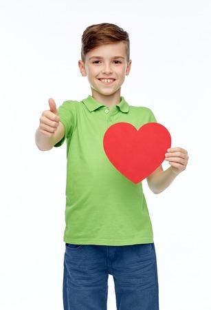 forme et sante: enfance, l'amour, la charité, les soins de santé et les gens concept - garçon souriant heureux t-shirt de polo vert tenant en blanc en forme de coeur rouge et montrant thumbs up Banque d'images
