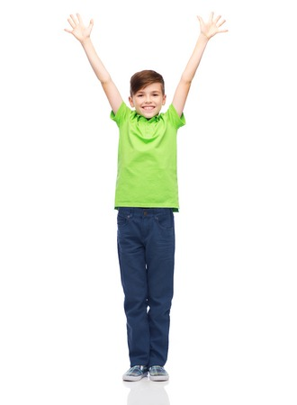 pre teen boys: childhood, fashion, power, joy and people concept - happy smiling boy in green polo t-shirt raising hands up Stock Photo