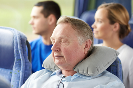 voyage: transport, tourism, comfort, road trip and people concept - senior man sleeping in travel bus with neck pillow Stock Photo