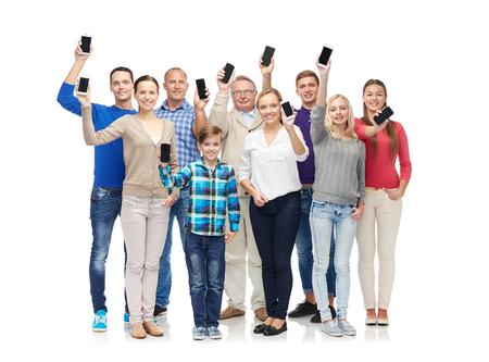 ludzie: Rodzina, technologia, produkcja i ludzie koncepcja - grupa uśmiechniętych mężczyzn, kobiet i chłopca smartfony