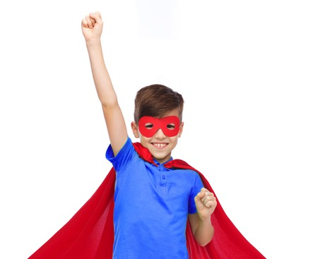 carnival, childhood, power, gesture and people concept - happy boy in red super hero cape and mask showing fists Stock Photo