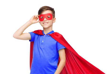 male costume: carnival, childhood, power, gesture and people concept - happy boy in red super hero cape and mask