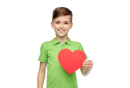 mother love: childhood, love, charity, health care and people concept - happy smiling boy in green polo t-shirt holding blank red heart shape Stock Photo