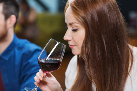 degustating: leisure, drinks, degustation, people and holidays concept - smiling woman drinking red wine at restaurant