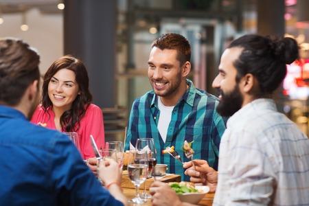 il tempo libero, cibo e bevande, le persone e le vacanze concetto - amici felici con cena al ristorante