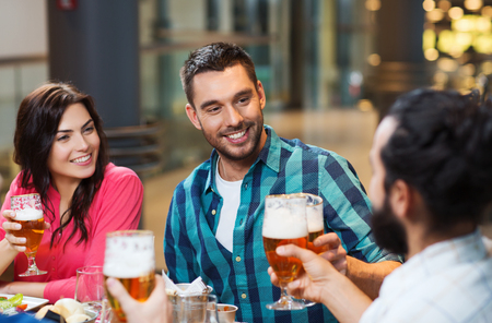 beer in bar: leisure, eating, food and drinks, people and holidays concept - smiling friends having dinner and drinking beer at restaurant or pub