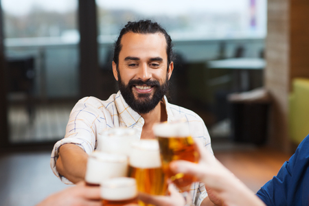 clinking: leisure, drinks, celebration, people and holidays concept - smiling man clinking beer glass with friends at restaurant