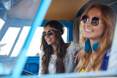 niñas sonriendo: vacaciones de verano, viaje por carretera, vacaciones, los viajes y el concepto de la gente - sonriendo mujer joven del hippie que conducen en coche monovolumen