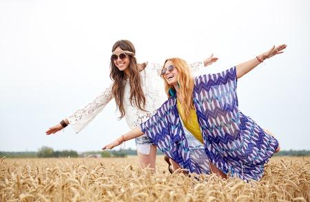 Natur, Sommer, Jugendkultur, Freundschaft und Menschen Konzept - lächelnde junge Frauen Hippie Spaß auf Getreidefeld mit Standard-Bild - 51496601