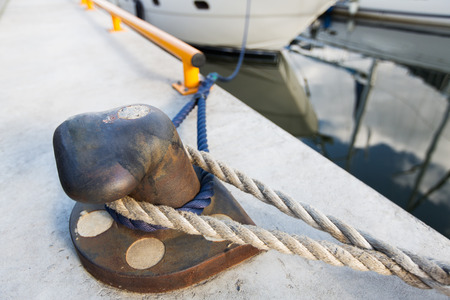 pawl: sailing, safety, mooring and water transport concept - rusted iron mooring bollard with rope on concrete pier