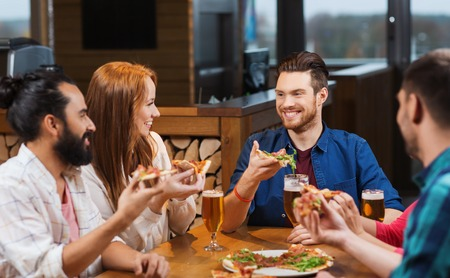 lunch food: leisure, food and drinks, people and holidays concept - smiling friends eating pizza and drinking beer at restaurant or pub Stock Photo